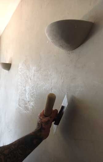Worker smoothing marble plaster