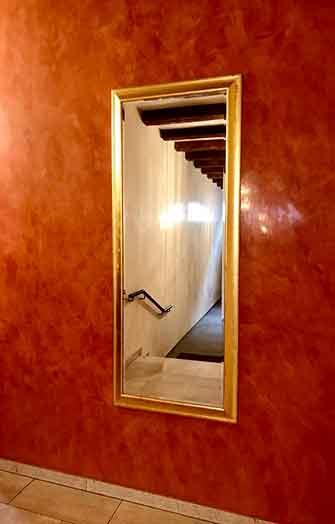 glänzende rote Wand mit Spiegel Goldrahmen